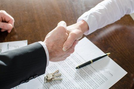 34423231 - estate agent shaking hands with his customer after contract signature