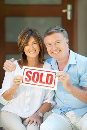 Happy mature couple holding sold sign in front of a new house